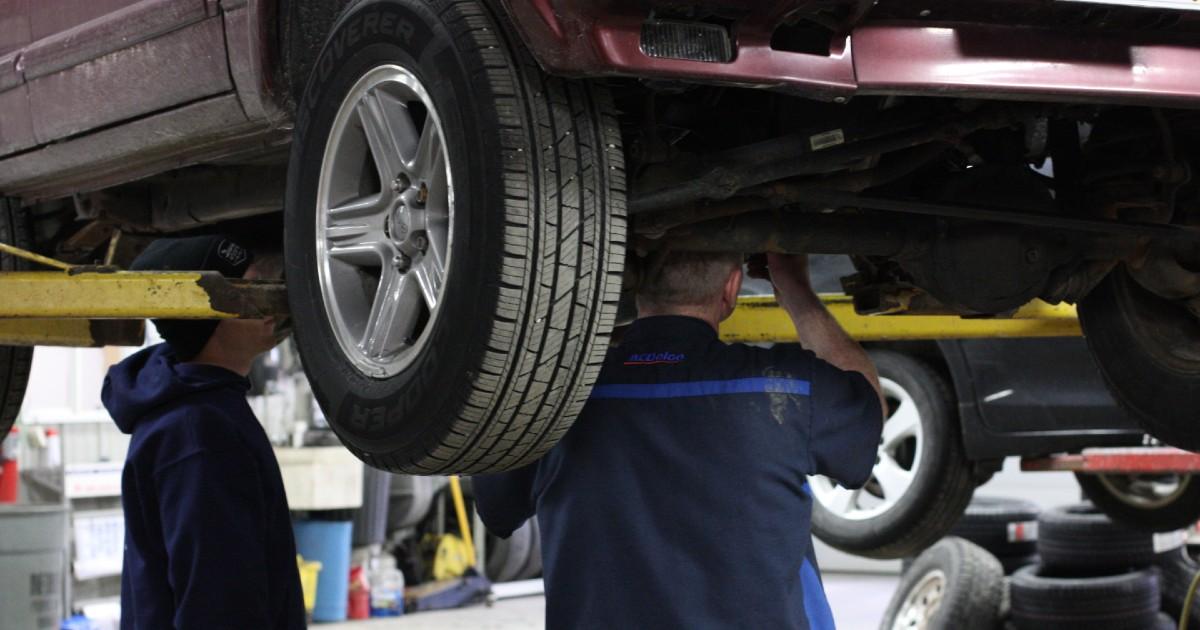 technicians under a car