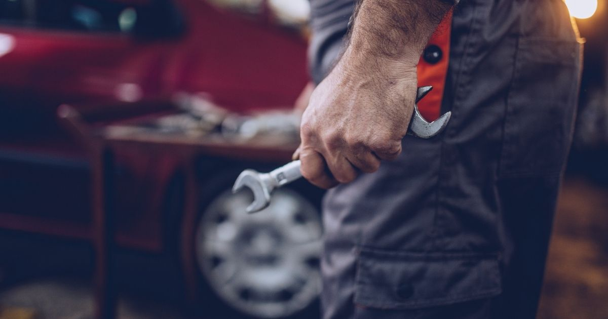 mechanic holding a wrench in an automotive repair shop